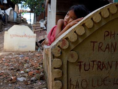 Seorang anak perempuan berbaring di atas sebuah kuburan di Phnom Penh, Kamboja pada 5 Juni 2019. Pemakaman menjadi tempat peristirahatan abadi bagi orang mati, tetapi area pemakaman ini menjelma sebagai tempat tinggal untuk bertahan hidup bagi mereka yang didera kemiskinan. (TANG CHHIN Sothy/AFP)