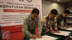 (ki-ka) Ketua Bawaslu Muhammad, Ketua KPU Juri Ardiantoro, Ketua KPI Yuliandre Darwis menandatangani Keputusan Bersama Antara Bawaslu, KPU, Dan KPI di Jakarta, Jumat (11/11). (Liputan6.com/Faizal Fanani)