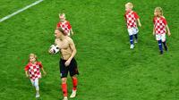 Bek Kroasia, Domagoj Vida bersama anak-anak pemain Kroasia berjalan di lapangan usai menundukkan Inggris di laga semifinal Piala Dunia 2018 di Stadion Luzhniki, Moskow, Rusia, Rabu (11/7). (MLADEN ANTONOV/AFP)