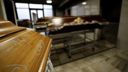 Sebuah peti mati bertanda COVID disiapkan untuk dibakar di krematorium di Ostrava, Republik Ceko pada 7 Januari 2021. Krematorium terbesar di Republik Ceko telah kewalahan dengan meningkatnya jumlah korban pandemi virus corona Covid-19. (AP Photo/Petr David Josek)