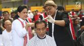 Presiden Joko Widodo disaksikan Ibu Negara Iriana saat mengikuti acara cukur rambut massal di Garut, Jawa Barat, Sabtu (19/1). Jokowi ikut cukur rambut bersama puluhan warga Garut lainnya. (Liputan6.com/Angga Yuniar)