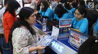 Petugas stan agen perjalanan melayani calon konsumennya pada pameran Garuda Indonesia Travel Fair (GATF) 2018 di Jakarta Convention Centre, Jumat (5/10). GATF memberikan potongan harga tiket perjalanan hingga 80%. (Liputan6.com/Angga Yuniar)