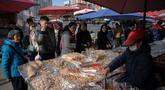 Sejumlah orang mengantre saat berbelanja kue di pasar di Beijing (20/11).  (AFP Photo/Nicolas Asfouri)