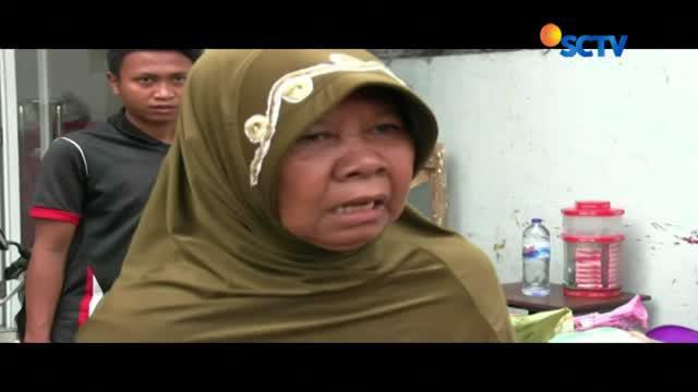 Salah seorang ibu mempertahankan gerobak dagangnnya agar tidak dibawa oleh petugas.