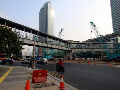 Suasana pembongkaran Jembatan Penyebrangan Orang (JPO) di Kawasan Bundaran HI, Jakarta, Senin (30/7). JPO yang sempat menimbulkan kontreversi itu dirobohkan karena alasan keindahan dan tak ramah penyandang disabilitas. (Liputan6.com/Johan Tallo)