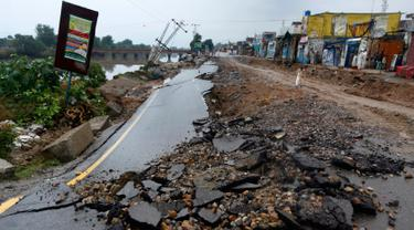 Seorang pria melintas dekat jalan yang rusak akibat gempa bumi yang melanda Jatla di dekat Mirpur, Rabu (25/9/2019).  Jalan-jalan yang rusak serta listrik yang padam menghambat upaya-upaya penyelamatan korban gempa bermagnitudo 5,8 tersebut. (AP Photo/Anjum Naveed)
