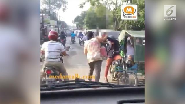 Seorang emak-emak asal Medan memukul tukang becak dengan helmnya, saat ia menyalip dan motornya terjepit becak.