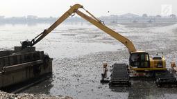 Alat berat milik Pemprov DKI Jakarta melakukan pengerukan endapan lumpur berikut sampah yang ada di Waduk Pluit, Jakarta, Selasa (11/6/2019). Pengerukan ini untuk mencegah terjadinya pendangkalan permukaan waduk. (Liputan6.com/Helmi Fithriansyah)