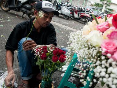 Pekerja merangkai bunga mawar di Pasar Bunga Rawa Belong, Jakarta, Selasa (14/2). Harga mawar saat Hari Valentine naik dua hingga tiga kali lipat, untuk bunga lokal yang biasanya dijual 25 ribu seikat menjadi 50 ribu seikat. (Liputan6.com/Gempur M Surya)