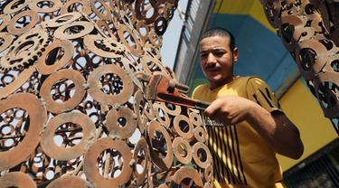 Ibrahim Salah membuat sebuah patung di bengkel kerjanya di Giza, Mesir, pada 5 September 2020. Dua pemuda Mesir berhasil mengubah hobi mereka mendaur ulang barang bekas seperti besi tua menjadi berbagai dekorasi dan furnitur rumah sebagai sumber penghasilan yang stabil. (Xinhua/Ahmed Gomaa)