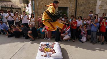 Pria berkostum setan melompati bayi-bayi yang terlentang di atas matras di sebuah jalan selama festival El Colacho di desa Castrillo de Murcia, bagian utara Spanyol, 23 Juni 2019. Festival melompati bayi ini sudah menjadi perayaan tahunan sejak tahun 1620. (CESAR MANSO/AFP)