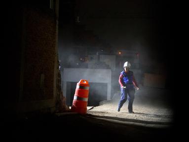 Seorang petugas penyelamat berjalan disamping bangunan garasi parkir bawah tanah yang runtuh di sebuah kompleks di Mexico City (10/4). Akibat insiden tersebut, sejumlah orang tewas dan masih terjebak di dalam. (AP Photo/Rebecca Blackwell)