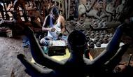Seorang perajin mengerjakan wajah patung tanah liat dewi Hindu Durga di sebuah lokakarya menjelang festival Durga Puja di Vashi di Navi Mumbai (23/9/2021). Durga Puja  adalah festival tahunan di Asia Selatan untuk memuja dewi Durga dari agama Hindu. (AFP/Indranil Mukherjee)
