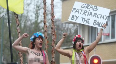 Dua orang wanita melakukan aksi telanjang dada memprotes kebijakan Presiden AS Donald Trump di sela-sela kunjungan Wakil Presiden AS, Mike Pence ke Belgia di Brussel, Senin (20/2). (AFP Photo/ JOHN THYS)