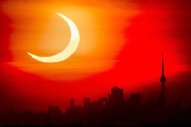 Gerhana matahari cincin muncul di atas cakrawala Toronto, Kamis (10/6/2021). Fenomena gerhana matahari cincin jatuh pada 10 Juni 2021. Gerhana matahari cincin menjadi fenomena yang dinanti setelah gerhana Bulan total pada 26 Mei 2021 lalu.  (Frank Gunn/The Canadian Press via AP)
