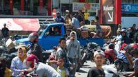 Sebuah mobil yang membawa peti mati dari kerabat mereka melintas saat warga menjarah toko serba ada setelah gempa dan tsunami di Palu, Sulteng, Minggu (30/9). Warga terpaksa mengambil karena membutuhkan makanan dan air bersih. (AFP PHOTO/BAY ISMOYO)