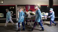 Petugas medis membawa pasien virus corona COVID-19 di Stasiun Gare d'Austerlitz di Paris, Prancis, Rabu (1/4/2020). Prancis mengerahkan kereta kecepatan tinggi untuk mengevakuasi pasien COVID-19 dari Paris ke wilayah Brittany. (Thomas SAMSON/AFP/POOL)