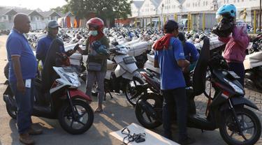 Petugas mengemas sepeda motor untuk diangkut dengan kereta api Stasiun Kampung Bandan, Jakarta, Senin (11/6). Program mudik gratis ini digagas Kemenhub tersebut melayani pengiriman ke beberapa daerah di Pulau Jawa. (Liputan6.com/Immanuel Antonius)