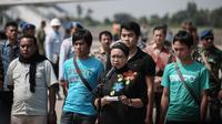 Lambaian tangan dan senyum terkembang dari wajah 4 WNI yang tiba sekitar pukul 10.24 WIB di Base Ops Lanud Halim Perdanakusuma, Jakarta. (Faizal Fanani/Liputan6.com)