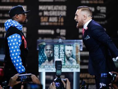Juara mixed martial arts Conor McGregor (kiri) dan petinju Floyd Mayweather Jr bertatapan saat jumpa pers di Staples Center Los Angeles, AS (12/7). Mayweather dan McGregor akan bertanding pada 26 Agustus 2017. (AP Photo/Jae C. Hong)