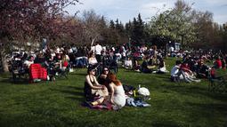 "Orang-orang duduk di sebuah taman di Ankara, sehari sebelum penerapan ""penguncian penuh"" atau lockdown, Rabu (28/4/2021). Turki akan memberlakukan lockdown penuh selama tiga minggu dari 29 April hingga 17 Mei 2021 untuk membendung penyebaran virus corona. (AP Photo/Burhan Ozbilici)"