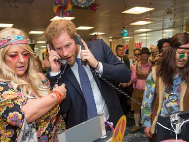 Pangeran Harry mengangkat dua telepon sekaligus saat menjadi broker dalam acara amal tahunan ICAP di London, Rabu (7/12). Pangeran Harry menjadi broker dadakan untuk mengumpulkan dana amal dari 60 kantor di seluruh dunia. (REUTERS/Geoff Pugh/Pool)