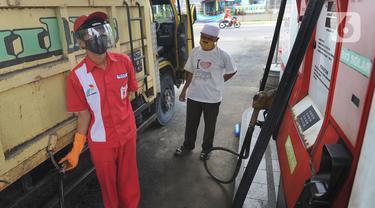 Petugas dengan sarung tangan, masker dan pelindung wajah melayani pembeli BBM di SPBU kawasan Cilendek, Bogor, Selasa (5/5/2020). Mencegah penularan Covid-19, sejumlah perusahaan memberikan pelindung diri kepada pegawai, terlebih yang berhubungan langsung dengan pelanggan. (merdeka.com/Arie Basuki)