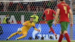 Kebuntuan Portugal akhirnya pecah pada menit ke-57 setelah Ronaldo sukses menjadi algojo tendangan pinalti. Portugal mendapatkan pinalti usai Danilo dijatuhkan di kotak terlarang Prancis. Papan skor berubah menjadi 1-0 dengan keunggulan Portugal. (Foto: AP/Pool/Franck Fife)