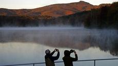 Pasangan mengambil foto saat matahari terbit di Price Lake sepanjang Blue Ridge Parkway dekat Blowing Rock, North California, saat musim gugur tiba, pada 19 Oktober 2021. (AP Photo/Gerry Broome)