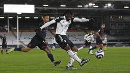 Pemain Fulham Andre-Frank Zambo Anguissa (tengah) menendang bola saat pemain Manchester City Gabriel Jesus mendekatinya pada pertandingan Liga Inggris di Stadion Craven Cottage, London, Inggris, Sabtu (13/3/2021). Manchester City menang 3-0. (Catherine Ivill/Pool via AP)
