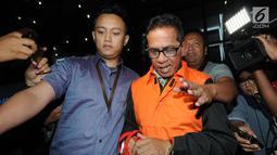 Bupati Mesuji, Khamami kenakan rompi tahanan dikawal petugas usai menjalani pemeriksaan 1x24 jam di gedung KPK, Jakarta, Jumat (25/1). Khamami ditahan 20 hari kedepan untuk memudahkan pemeriksaan. (merdeka.com/Dwi Narwoko)