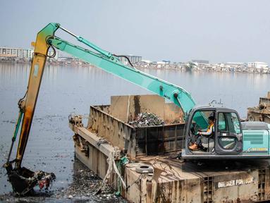 Kendaraan eskavator dan tongkang Dinas Tata Air DKI Jakarta mengeruk lumpur dan sampah dari Waduk Pluit, Jakarta, Selasa (11/12). Pengerukan ini rutin dilakukan oleh Dinas Tata Air DKI Jakarta. (Liputan6.com/Faizal Fanani)