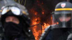 Polisi anti huru hara berjaga dengan latar belakang api yang menyala saat terjadi aksi demonstrasi pada peringatan Hari Buruh di Paris, Prancis (1/5). Hari Buruh yang jatuh pada tanggal 1 Mei ini diperingati di berbagai negara. (AFP/Alain Jocard)