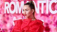 """Penyanyi dan artis Hollywood, Miley Cyrus berpose saat tiba menghadiri pemutaran perdana film """"Isn't It Romantic"""" di Los Angeles (11/2). Miley Cyrus tampil memesona dengan gaun berwarna merah Maison Valentino. (AFP Photo/Jean-Baptiste Lacroix)"""