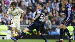Bek Real Madrid, Alvaro Odriozola, berusaha melewati bek Real Valladolid, Fernando Calero, pada laga La Liga Spanyol di Stadion Santiago Bernabeu, Madrid, Sabtu (3/11). Madrid menang 2-0 atas Valladolid. (AFP/Javier Soriano)