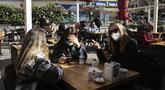 Para perempuan mengobrol sambil menunggu pesanan mereka di restoran yang dibuka kembalidi Ankara, Turki, Selasa (2/3/2021). Aktivitas bisnis seperti kafe dan restoran, diizinkan dibuka kembali dengan pembatasan kapasitas jumlah pengunjung serta jam operasional. (AP Photo/Burhan Ozbilici)
