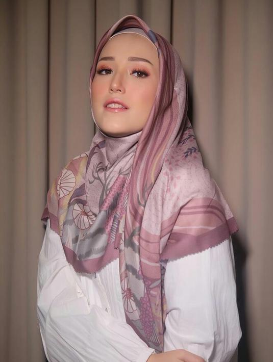 Hijab segi empat satin yang kamu bentuk jadi loose akan memberikan kesan tampilan yang mewah. Buat salah satu sisi hijab lebih pendek, dan tarik sisi hijab yang panjang ke samping. (Instagram.com/adeliapasha).