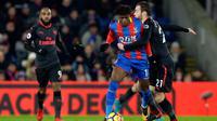 Pemain Arsenal, Calum Chambers berusaha menahan pemain Crystal Palace Wilfried Zaha saat pertandingan Liga Inggris di stadion Selhurst Park di London (28/12). (AP Photo/Alastair Grant)
