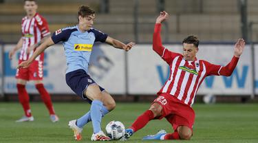 Gelandang Borussia Monchengladbach, Florian Neuhaus, berebut bola bek SC Freiburg, Robin Koch, pada laga lanjutan Bundesliga di Freiburg, Jumat (5/6/2020) waktu setempat. Monchengladbach kalah 0-1 atas Freiburg. (AFP/Ronald Wittek/Pool)