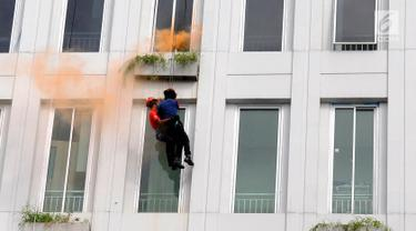 Petugas menyelamatkan pria saat simulasi penanggulangan korban kebakaran dan gempa bumi di Balai Kota Tangerang Selatan, Banten, Kamis (26/4). Simulasi diikuti oleh Petugas Damkar dibantu PMI dan  BPBD Kota Tangerang Selatan. (Merdeka.com/Arie Basuki)