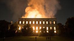 Warga menyaksikan kebakaran yang melanda Museum Nasional Brasil berusia 200 tahun di Rio de Janeiro, Minggu (2/9). Museum itu didirikan pada 1818 oleh Raja Joao VI dan merupakan salah satu museum terpenting di Brasil. (AP/Leo Correa)