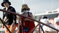 Turis China menggunakan masker saat tiba di Nusa Penida, Bali. (dok. foto SONNY TUMBELAKA/AFP)