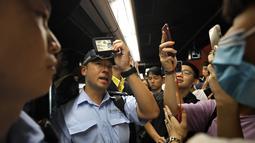 Seorang perwira polisi menunjukkan kartu anggotanya setelah pemrotes memintanya di sebuah stasiun kereta bawah tanah di Hong Kong (30/7/2019). Para Pengunjuk rasa telah mengganggu layanan kereta bawah tanah pada pagi hari. (AP Photo/Vincent Yu)