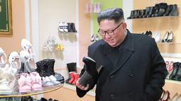 Pemimpin Korea Utara, Kim Jong-Un melihat salah satu sepatu saat mengunjungi pabrik sepatu Wonsan, Korea Utara (3/12). (Photo by KCNA VIA KNS / various sources / AFP)
