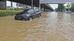 Sebuah mobil melintasi banjir di Jalan Ahmad Yani, Cempaka Putih, Jakarta, Minggu (23/2/2020). Banjir yang terjadi dari dini hari tadi melumpuhkan akses jalan tersebut. (Liputan6.com/Herman Zakharia)
