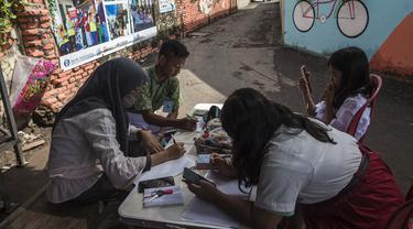 Siswa menggunakan gawai untuk mengikuti kegiatan belajar mengajar secara daring di tempat pembuangan sampah yang menyediakan WiFi gratis, di Surabaya, Rabu (15/9/2021). Belajar secara virtual itu sudah berjalan lebih dari setahun lebih di tengah pandemi Covid-19. (JUNI KRISWANTO/AFP)