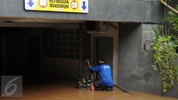 Petugas Damkar PB mengawasi kondisi mesin penyedot air saat melakukan pengeringan di salah satu pertokoan, Jalan Kemang Raya, Jakarta, Minggu (28/8). Dua lokasi parkir bawah tanah pertokoan di kawasan Kemang terendam air. (Liputan6.com/Helmi Fithriansyah)