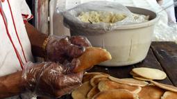 "Seorang pedagang Suriah membuat ""Qatayef"", penganan manis tradisional yang biasa disajikan saat bulan suci Ramadan di Damaskus, Suriah, (18/5/2020). (Xinhua/Ammar Safarjalani)"