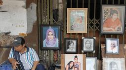 Seorang pelukis menunggu calon pemesan di trotoar Kawasan Glodok, Jakarta, Selasa (15/5). Bagi warga yang ingin dilukis, biasanya harus menyerahkan foto sebagai contoh materi lukisan. (Liputan6.com/Herman Zakharia)