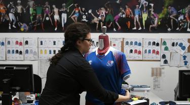 Pekerja memakaikan seragam timnas sepak bola Islandia rancangan Errea pada maneken di Torrile, dekat Parma, Italia Utara, (20/4). Seragam timnas Islandia ini merupakan rancangan perusahaan apparel olahraga asal Italia. (AFP Photo/Marco Bertorello)